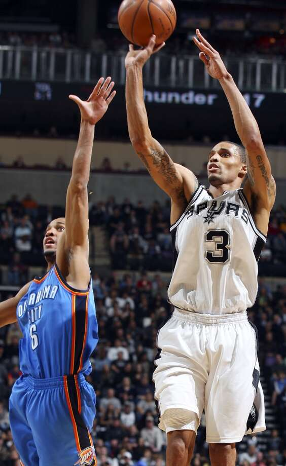 The Spurs' George Hill shoots around Thunder's Eric Maynor during first half action Saturday Jan. 1, 2011 at the AT&T Center.
