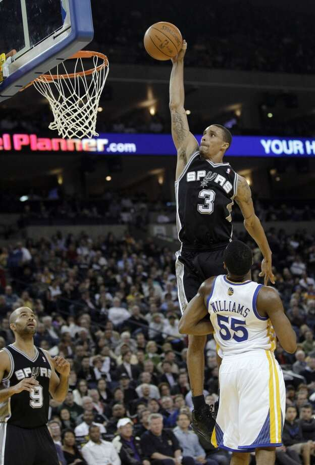The Spurs' George Hill (3) goes up for a dunk next to Golden State Warriors' Reggie Williams (55) during the first half of an NBA basketball game in Oakland, Calif., Monday, Jan. 24, 2011.