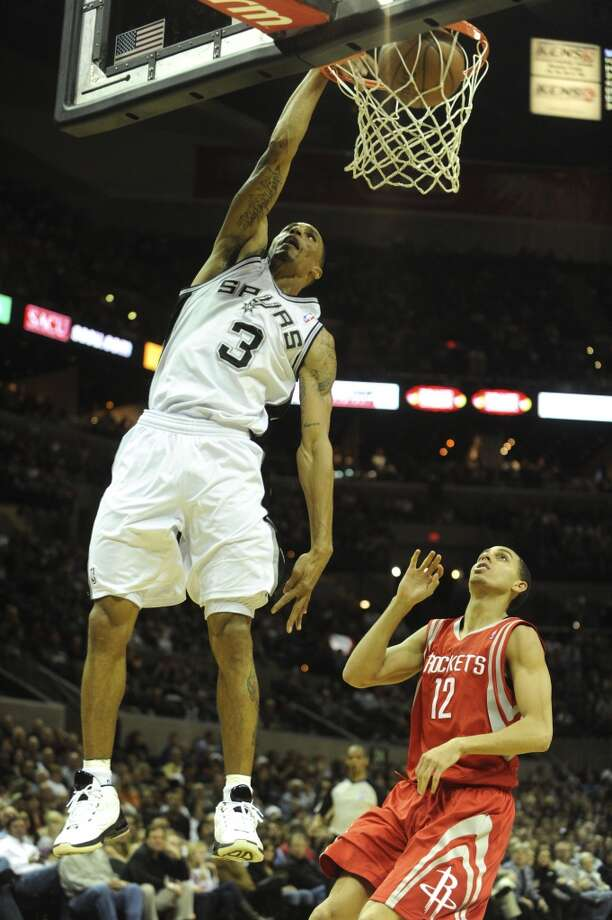 George Hill of the Spurs dunks to end a breakaway as Kevin Martin of the Rockets gives chase during NBA action at the AT&T Center on Saturday, Jan. 29, 2011.