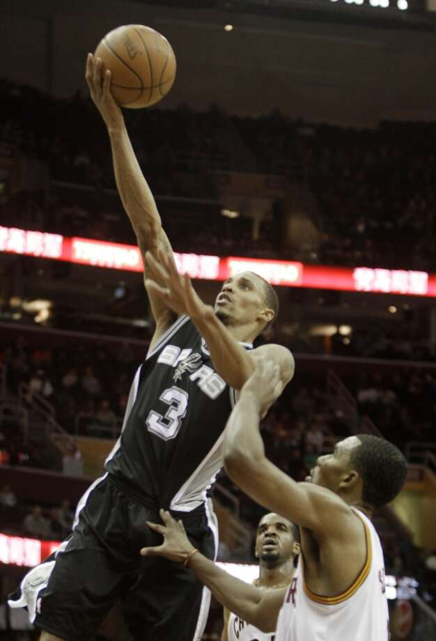 The Spurs' George Hill (3) shoots over the Cavaliers' Samardo Samuels (24) and Ramon Sessions in the second quarter in an NBA basketball game Wednesday, March 2, 2011, in Cleveland. Hill tied a season-high with 22 points for the Spurs' 109-99 win.