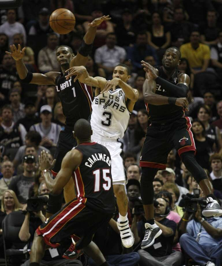 Spurs guard George Hill (3) passes away from Heat forward Chris Bosh (1), Heat guard Dwyane Wade (3) and Heat guard Mario Chalmers (15) during the second half of their NBA game at the AT&T Center on Friday, March 4, 2011.