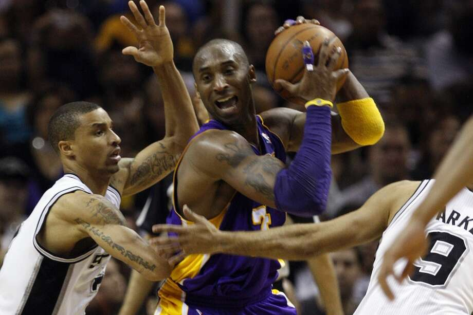 The Lakers' Kobe Bryant handles the ball under pressure from Spurs George Hill during the second half at the AT&T Center, Sunday, March 6, 2011. The Lakers won 99-83.