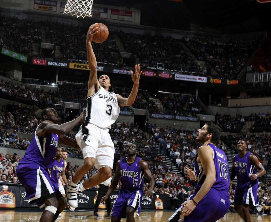 The Spurs' George Hill shoots between Kings defenders during first half action Friday March 11, 2011 at the AT&T Center.