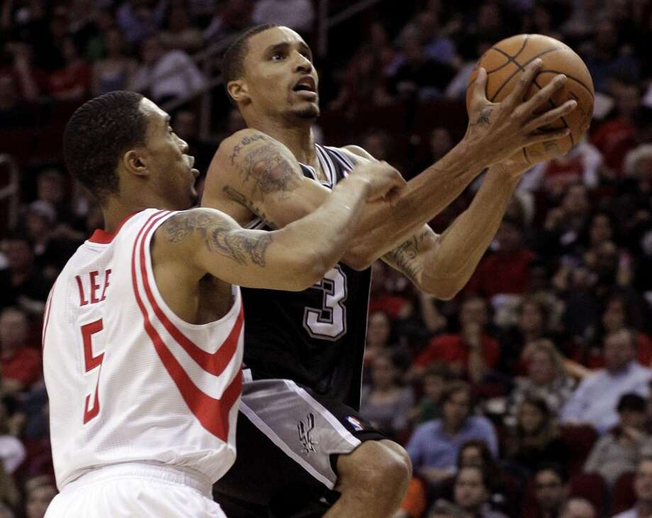 The Rockets' Courtney Lee (5) tries to stop the Spurs' George Hill (3) from scoring during the first half of an NBA basketball game on Saturday, March 12, 2011, in Houston.