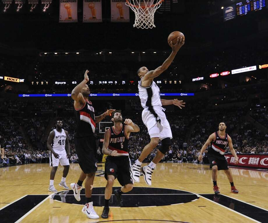 The Spurs' George Hill shoots between the Trail Blazers' Marcus Camby, Rudy Fernandez and  Brandon Roy during second half action Monday March 28, 2011 at the AT&T Center. The Trail Blazers won 100-92.
