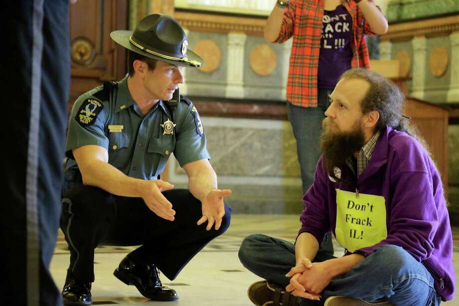 An Illinois State Capitol police officer speaks with Josh Trost, who is protesting against hydraulic fracturing in the state. Photo: Seth Perlman, STF / AP