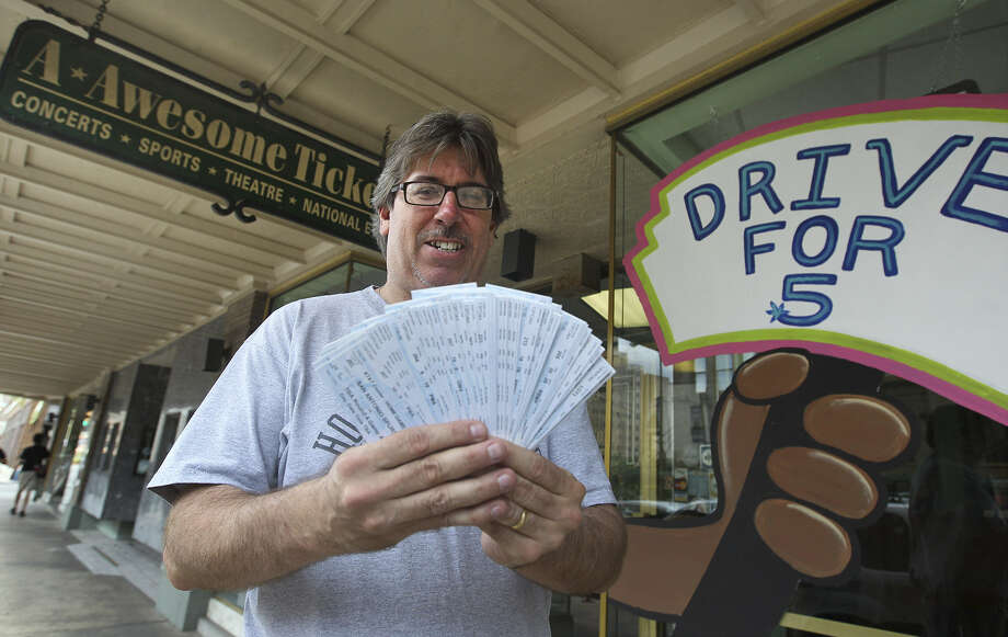 John Binder, owner of A-Awesome Tickets on Broadway, holds a stack a tickets for the NBA Finals. Photo: Kin Man Hui / San Antonio Express-News