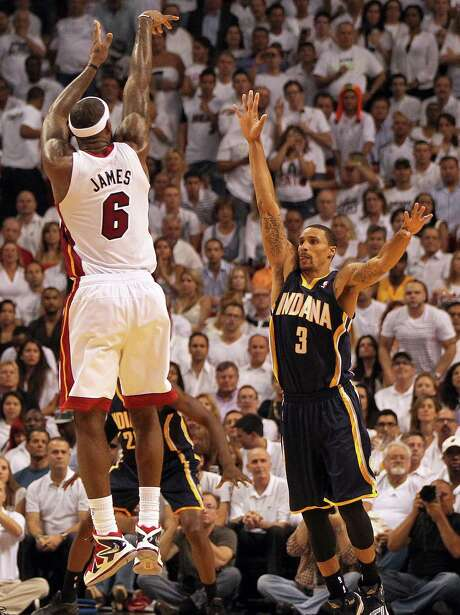 Miami's LeBron James launches a 3-pointer over Indiana's George Hill during the Heat's big third quarter Thursday night. The Heat outscored the Pacers 30-13 in the period en route to a crucial victory in Game 5. Photo: Pedro Portal / McClatchy-Tribune News Service