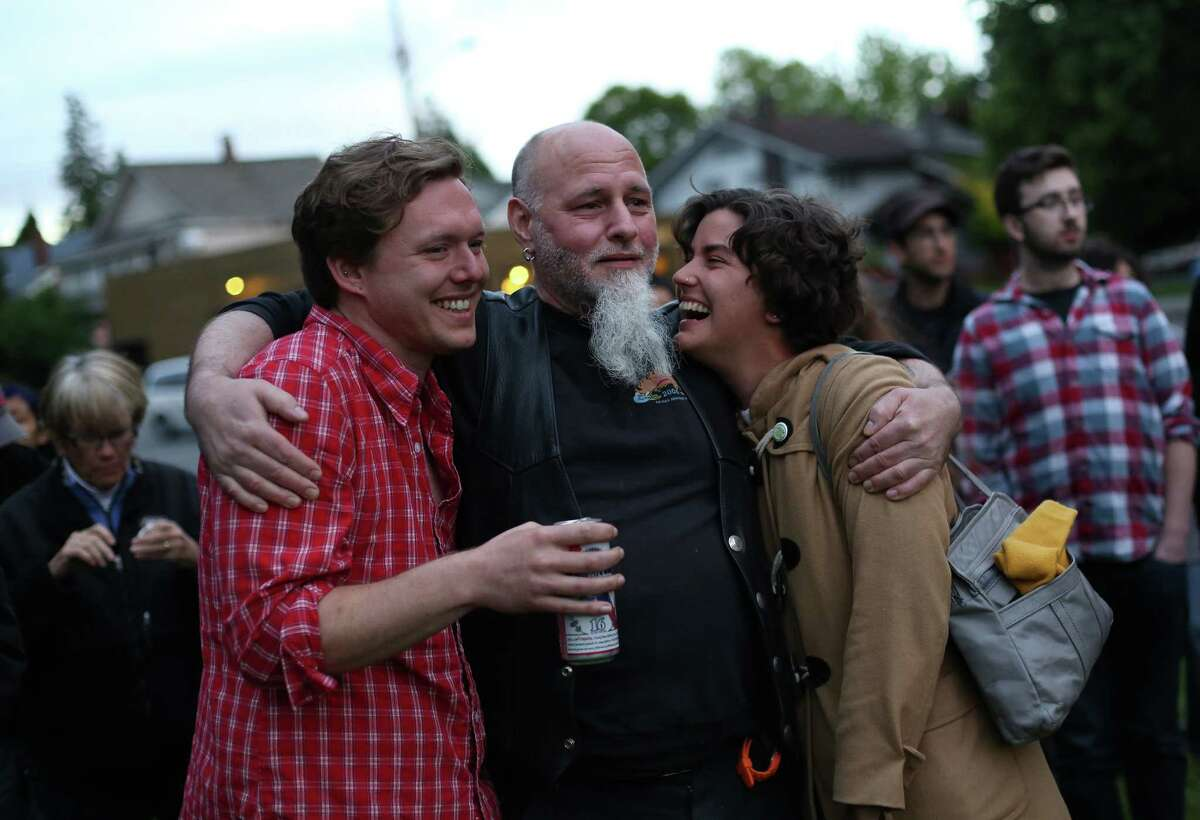 Cafe Racer survivor Leonard Meuse, center, embraces Dustin McMahon and Anny Schill during a memorial march and concert on Thursday, May 30, 2013, the one year anniversary of the shootings that left four people dead in the popular cafe. Dozens of people marched to music from the band Orkestar Zirkonium from Cafe Racer to nearby Cowen Park.