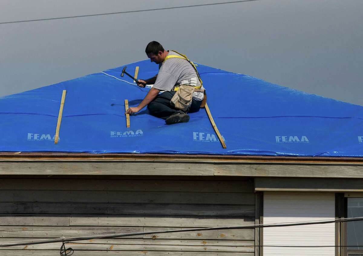 Dexter Stuart installs a blue roof tarp from FEMA to a home after damage from hurricane Ike in the Palm Beach subdivision Monday, Oct. 6, 2008, in Galveston. ( James Nielsen / Chronicle )
