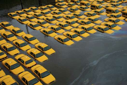 A parking lot full of yellow cabs is flooded as a result of superstorm Sandy on Tuesday, Oct. 30, 2012 in Hoboken, NJ. Photo: Charles Sykes, AP / 2012 The Associated Press