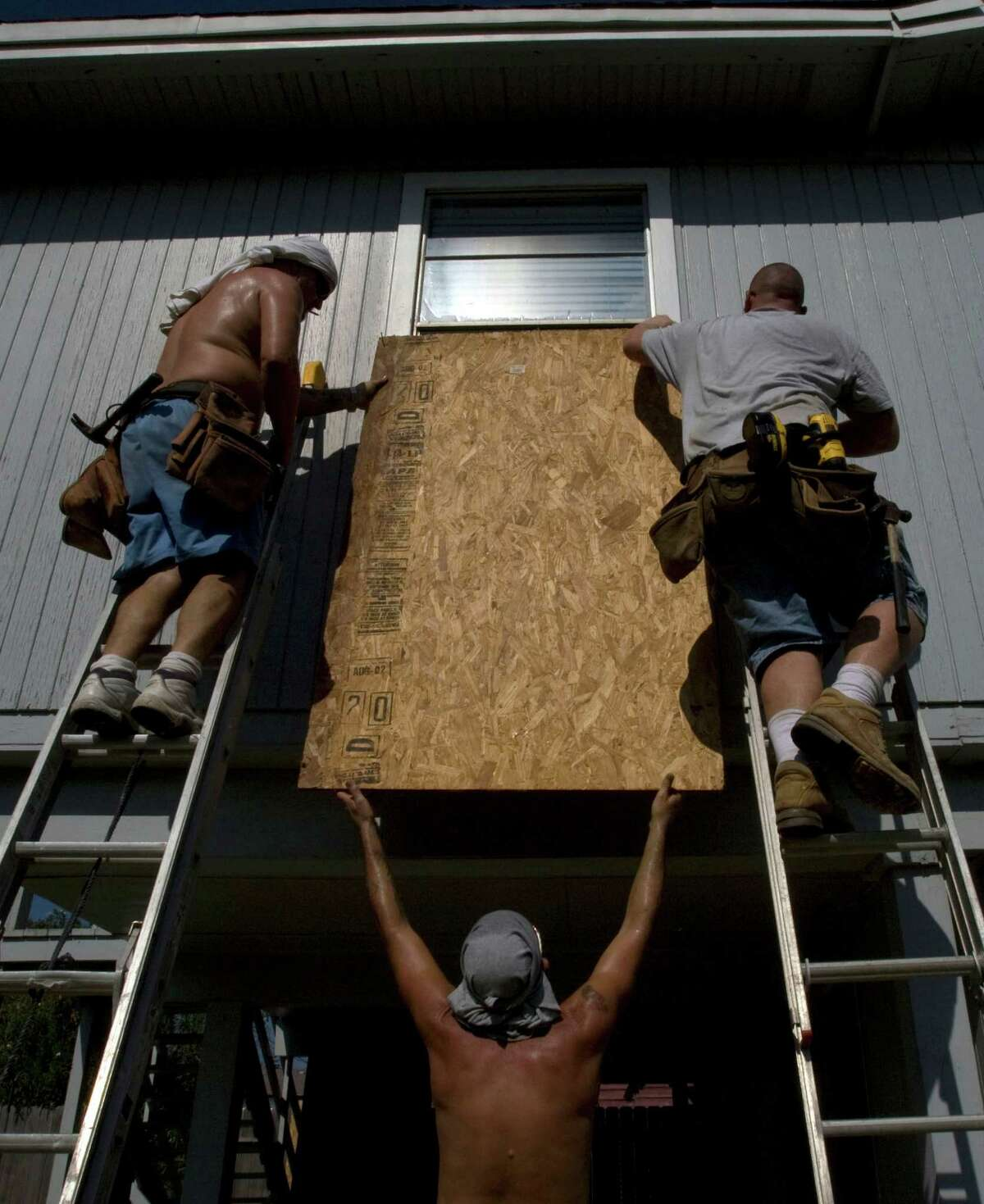"""Sam Broadway (left), Ian Brown (right) and Gary Kimbrell (center), with Sawyer Construction board up a home on Jamica Beach in preparation for Hurricane Ike, Wednesday, Sept. 10, 2008. """"We've done four and we've got 10 more to do,"""" Kimbrell said. ( Johnny Hanson / Chronicle )"""