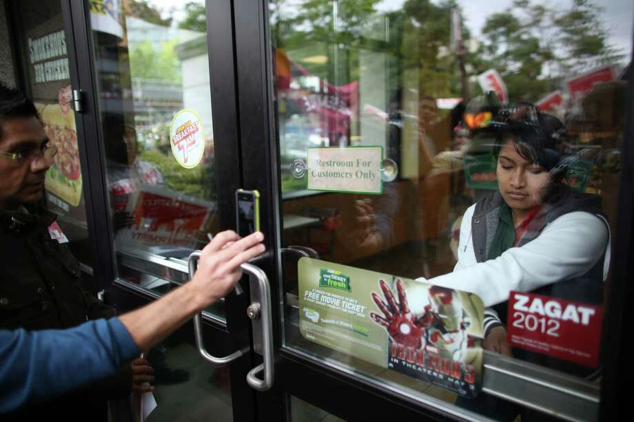 Subway worker Sofia Garcia locks up the restaurant as she walks off the job with other employees at the restaurant in Fisher Plaza on Thursday, May 30, 2013. The workers were encouraged to walk off the job by a large group of protesters. The group was asking for higher wages for fast food workers and to allow them to organize without retaliation. Hundreds of people participated in a march after a day of strikes at fast food restaurants around Seattle. Photo: JOSHUA TRUJILLO, SEATTLEPI.COM / SEATTLEPI.COM