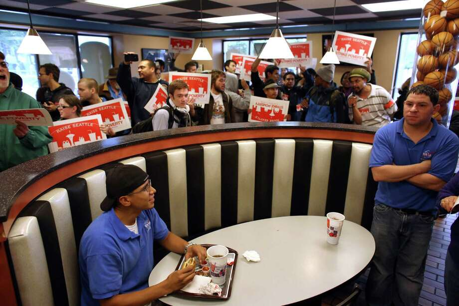 Customers try to eat as labor organizers and fast food workers gather inside a McDonald's restaurant near the Space Needle on Thursday, May 30, 2013. The group was asking for higher wages for fast food workers and to allow them to organize without retaliation. Hundreds of people participated in a march after a day of strikes at fast food restaurants around Seattle. Photo: JOSHUA TRUJILLO, SEATTLEPI.COM / SEATTLEPI.COM