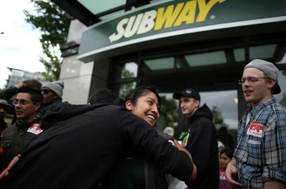 Subway worker Sofia Garcia is hugged after she locked up the restaurant and walked off the job with other employees at the restaurant in Fisher Plaza on Thursday, May 30, 2013. The workers were encouraged to walk off the job by a large group of protesters. The group was asking for higher wages for fast food workers and to allow them to organize without retaliation. Hundreds of people participated in a march after a day of strikes at fast food restaurants around Seattle. Photo: JOSHUA TRUJILLO, SEATTLEPI.COM / SEATTLEPI.COM