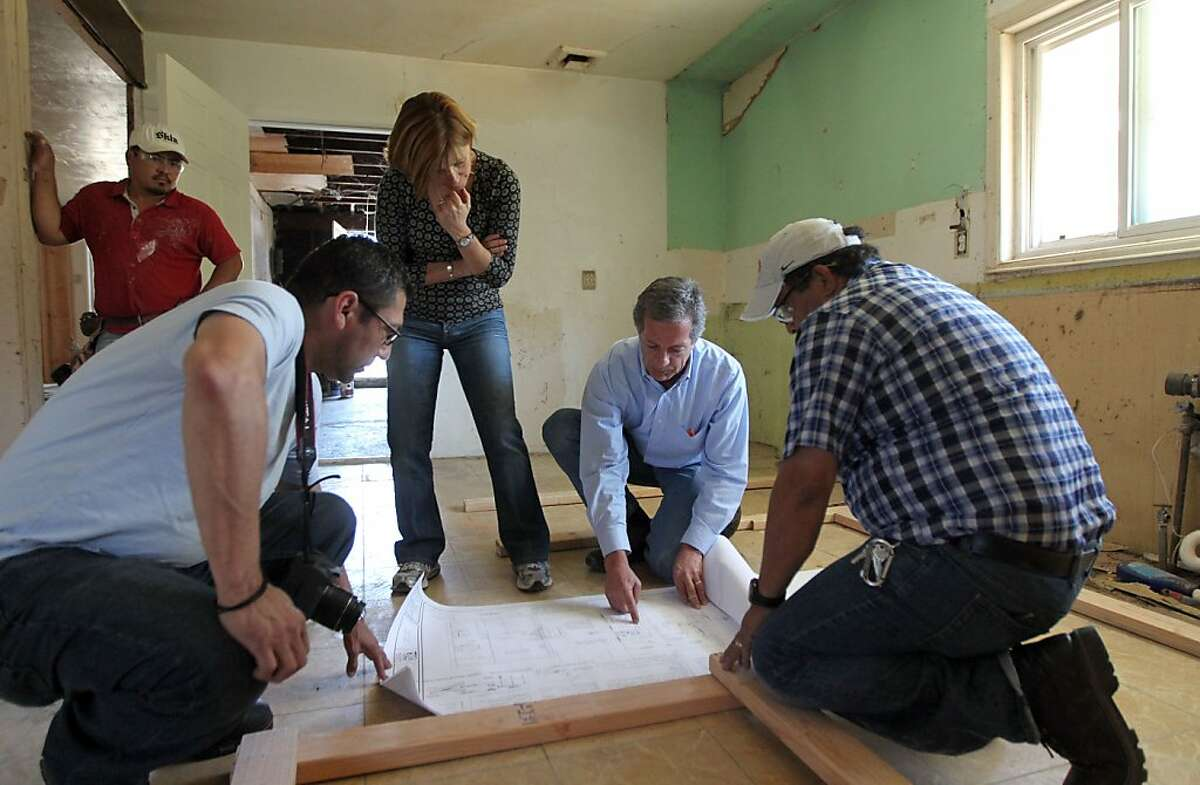 David Waal, second from right, principal of Presidio Realty Advisors, works on the plans for a new kitchen island with employees of Redwood National Construction at a Martinez home he and his company plan to re-sale Thursday, May 22, 2013 in Martinez Calif.