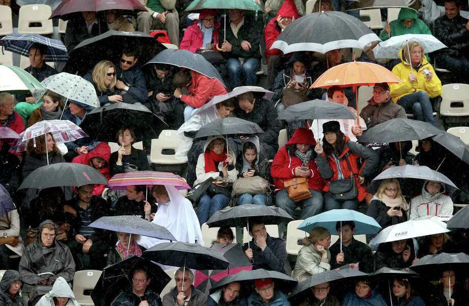 PARIS, FRANCE - MAY 30:  Spectators shelter under umbrellas as rain starts to fall during day five of the French Open at Roland Garros on May 30, 2013 in Paris, France.  (Photo by Matthew Stockman/Getty Images)  *** BESTPIX *** Photo: Matthew Stockman, Getty Images / 2013 Getty Images