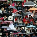 PARIS, FRANCE - MAY 30:  Spectators shelter under umbrellas as rain starts to fall during day five of the French Open at Roland Garros on May 30, 2013 in Paris, France.  (Photo by Matthew Stockman/Getty Images)  *** BESTPIX ***