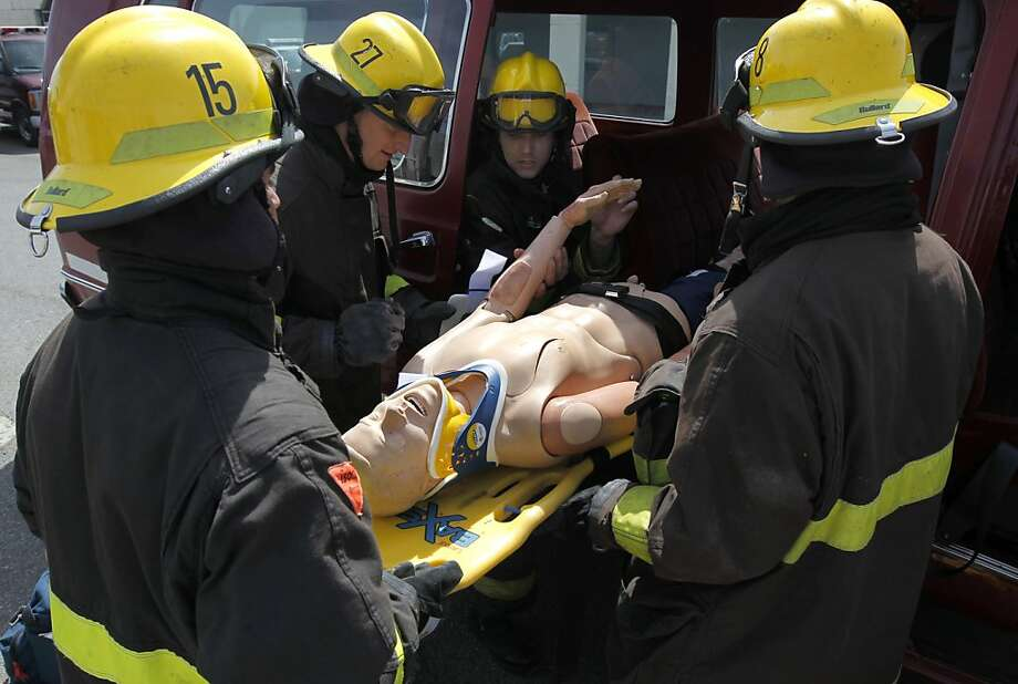 Students rescue a victim from a simulated auto accident at a City College firefighter training class on Treasure Island. The college's fire science cadet program includes 15 weeks of training in a fire station. Photo: Paul Chinn, The Chronicle