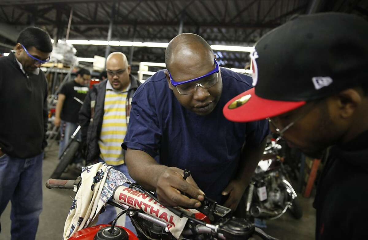 James Griffin (second from right) works on his motorcycle during an introduction to motorcycle mechanics class at the City College of San Francisco Evans Campus on Monday, April 15, 2013 in San Francisco, Calif.