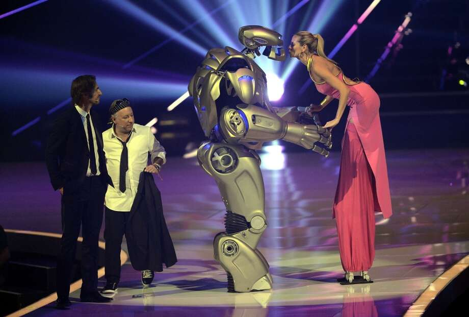 "Model and presenter Heidi Klum (r) gets a kiss from the roboter next to Enrique Badulescu (l) and Thomas Hayo (2.l) reacts during the final of 'Germany's Next Top Model' TV show at SAP Arena on May 30, 2013 in Mannheim, Germany. The four finalist Sabrina Elsner, Luise Will, Lovelyn Enebechi and Maike van Grieken fight under the motto  ""Closer than ever"" for the top model crown.  (Photo by Thomas Lohnes/Getty Images)"