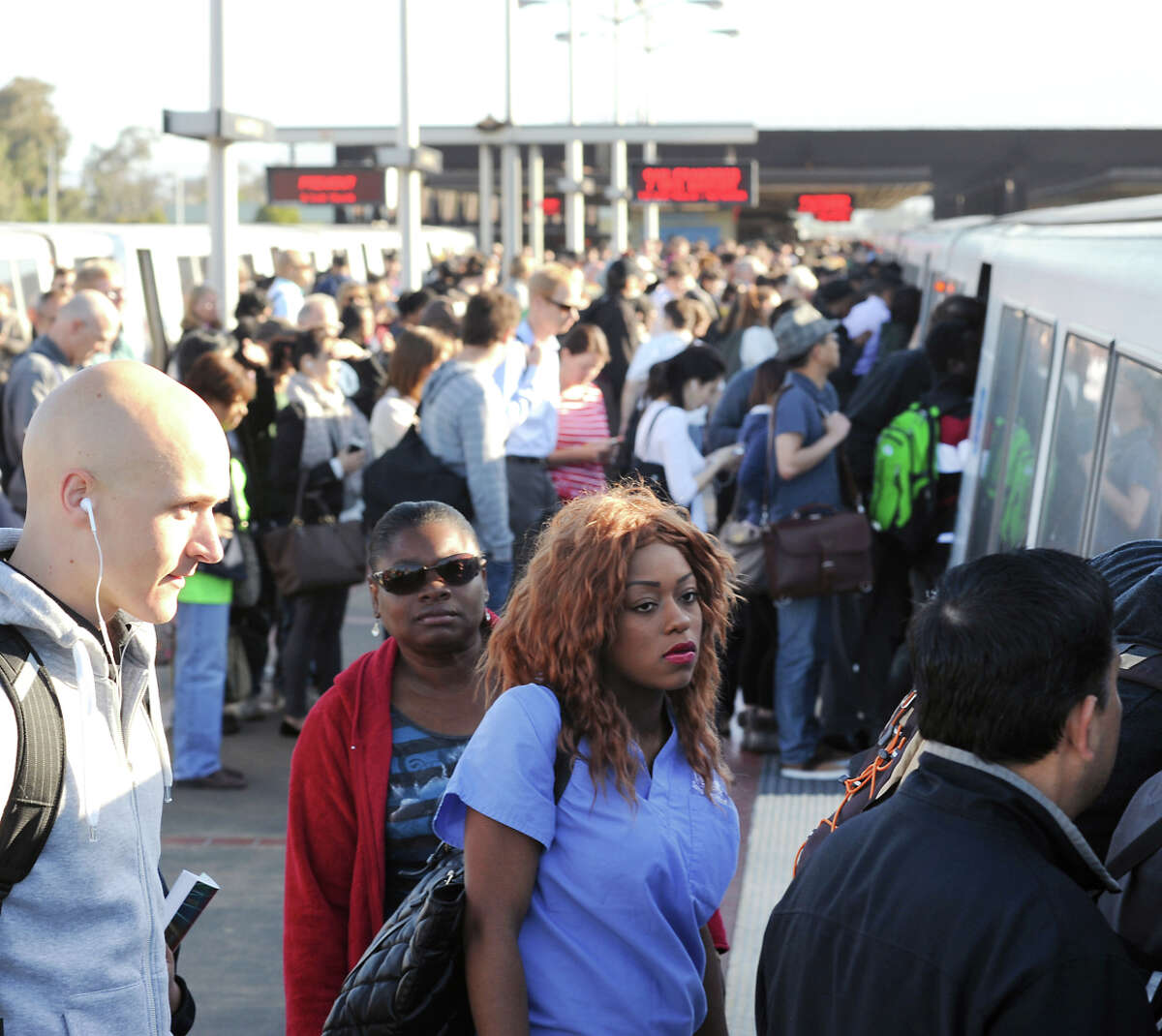 Commuters crowd S.F.-bound BART trains at MacArthur Station in Oakland. A second Transbay Tube through the heart of San Francisco could help riders.