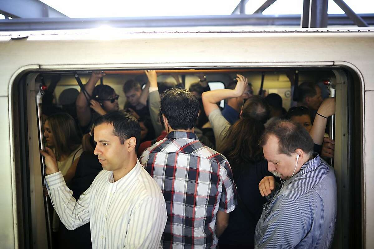 Crowds of tightly packed commuters aboard a BART train as it waits to leave the MacArthur station.
