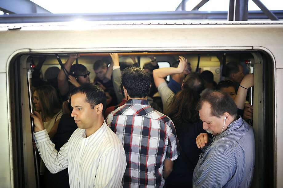 Commuters crowd into an S.F.-bound train as it waits to leave the MacArthur BART Station. Riders suffered through a brutally slow slog to get to work. Photo: Michael Short, Special To The Chronicle