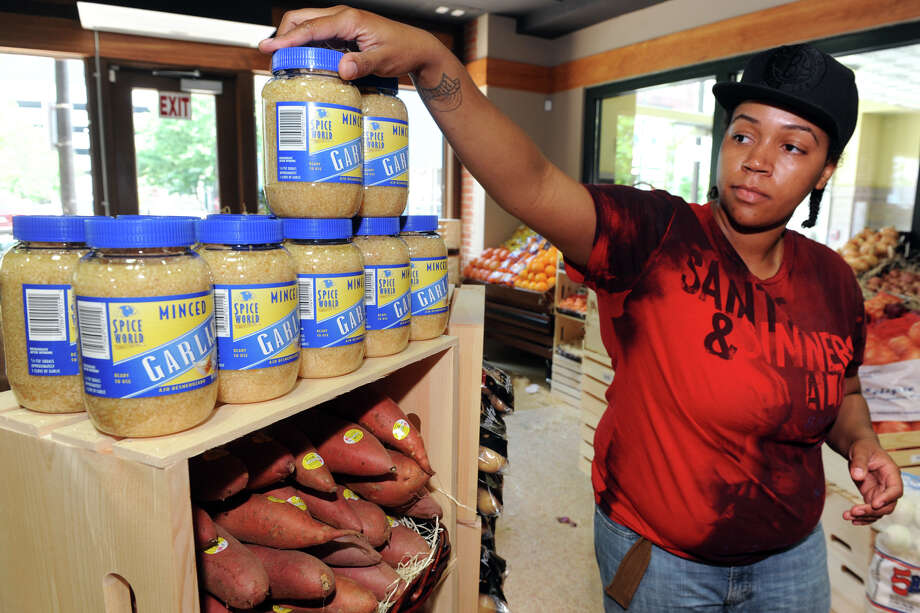 Shaneese Pettway stocks shelves at Ripka's Market, which will open soon in downtown Bridgeport, Conn., May 31st, 2013. Photo: Ned Gerard / Connecticut Post