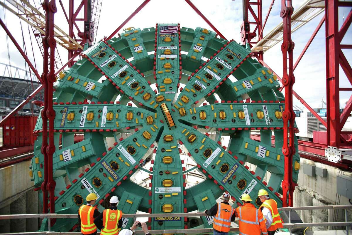 People watch as the cutter head of the Washington State Department of Transportation's Big Bertha Highway 99 tunnel boring machine is lowered into its launch pit on Friday, May 31, 2013. The machine is scheduled to be launched in July and will emerge from the other end of the tunnel 14 months later.
