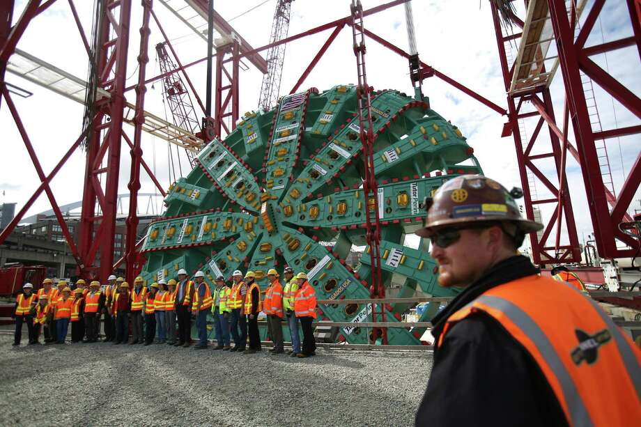 Workers and officials pose for a photo as the cutter head of the Washington State Department of Transportation's Big Bertha Highway 99 tunnel boring machine is lowered into its launch pit on Friday, May 31, 2013. The machine is scheduled to be launched in July and will emerge from the other end of the tunnel 14 months later. Photo: JOSHUA TRUJILLO, SEATTLEPI.COM / SEATTLEPI.COM