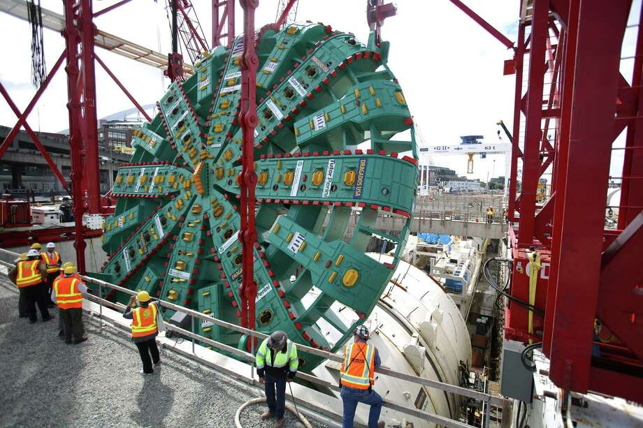 People look into the pit as the cutter head of the Washington State Department of Transportation's Big Bertha Highway 99 tunnel boring machine is lowered into its launch pit on Friday, May 31, 2013. The machine is scheduled to be launched in July and will emerge from the other end of the tunnel 14 months later. Photo: JOSHUA TRUJILLO, SEATTLEPI.COM / SEATTLEPI.COM