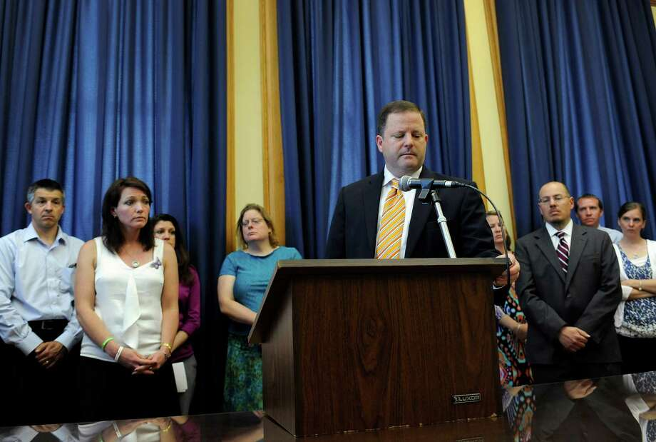 State Sen. Minority Leader John McKinney, R-Fairfield, and representing Newtown, answers questions from the media as families of victims from the Sandy Hook School shooting stand behind him during a news conference at the Capitol in Hartford, Conn., Friday, May 31, 2013.  Family members of the school shooting victims are making a last-minute appearance at the state Capitol to urge Connecticut legislators to pass a bill that would block the public release of crime scene photos and other records from the massacre. Photo: Jessica Hill, AP Photo/Jessica Hill / AP2013 Associated Press