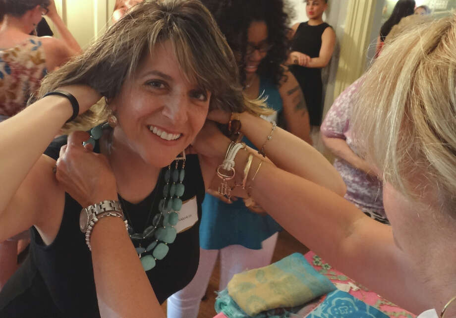 Karen Guastelle of Fairfield tries on jewelry by Jenny Boston at the Junior Women's Club of Fairfield's Ladies Night Out event on Thursday. Photo: Mike Lauterborn / Fairfield Citizen contributed