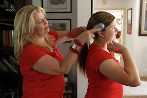 Kelly Lozano (left) helps her 14-year-old daughter, Samantha, as they prepare to attend a Taylor Swift concert.
