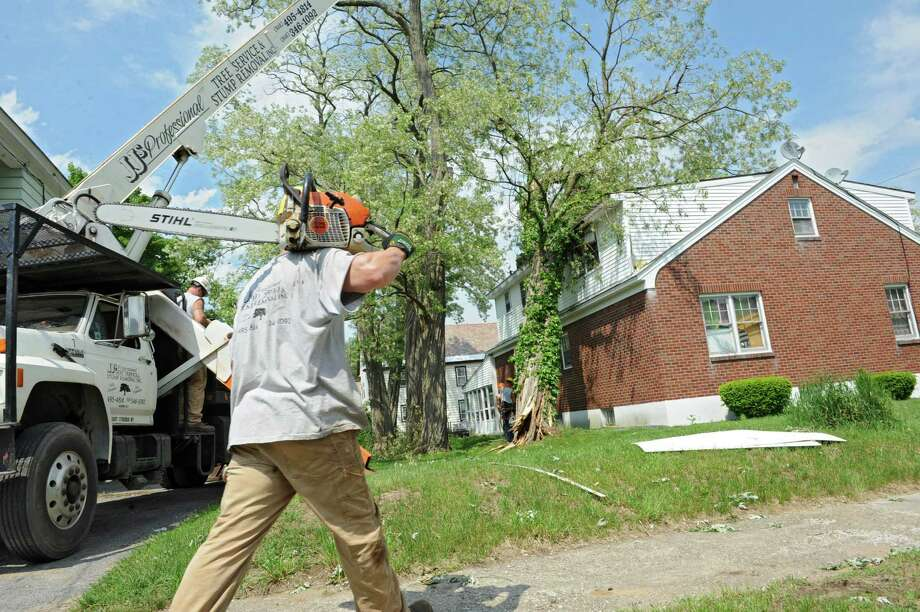 Gordon Saturday of JJ's Professional Tree Service and Stump Removal Inc. carries a chain saw to a house where a huge tree fell on it during a recent storm on Friday, May 31, 2013 in Schenectady, N.Y.  (Lori Van Buren / Times Union) Photo: Lori Van Buren