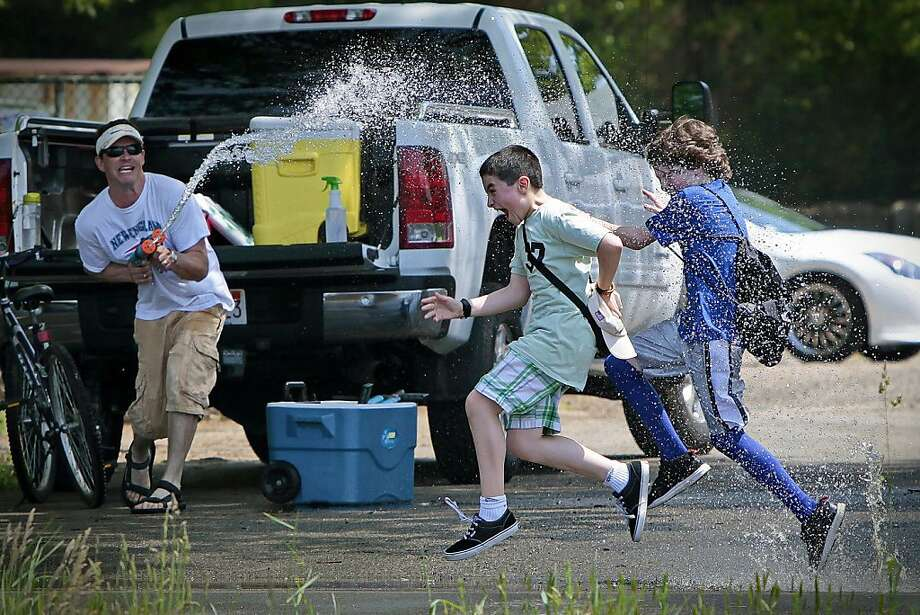 Surprise soak: In Rochester, Mass., Tom Forcier ambushes schoolchildren running in the Miles for Memorial School Kid's Fitness Challenge to cool them off. Or maybe he just enjoys the reactions. Photo: Peter Pereira, Associated Press