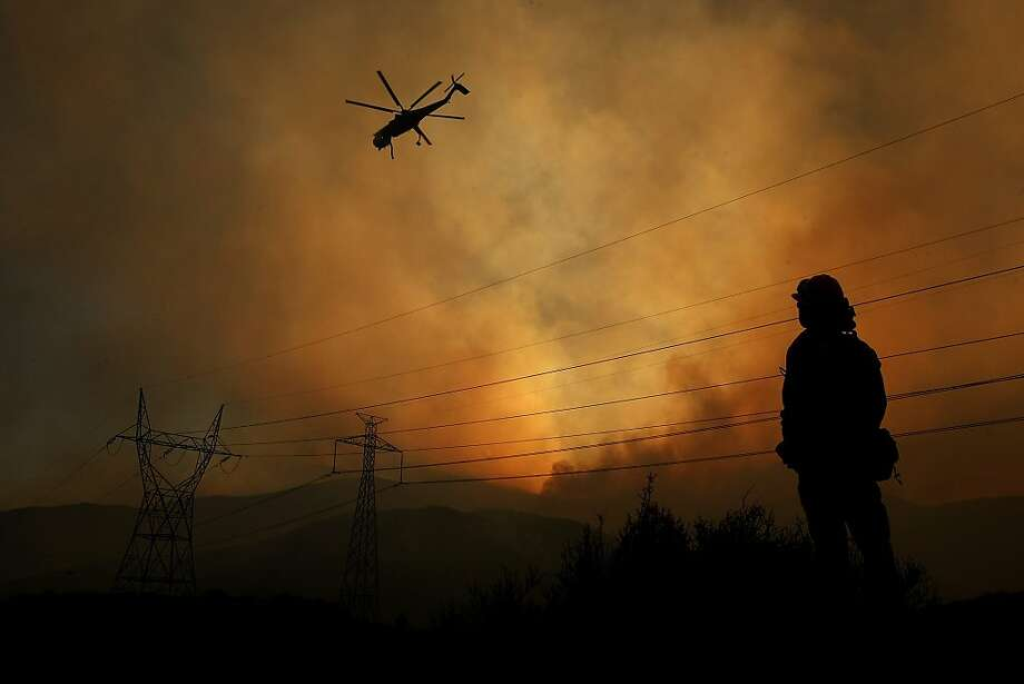 Weakening a Power House:Fire Capt. Gus Munguia watches as a helicopter prepares to drop a load of water on the Power House Fire, which has burned hundreds of acres in Green Valley, Calif. Photo: Genaro Molina, Associated Press