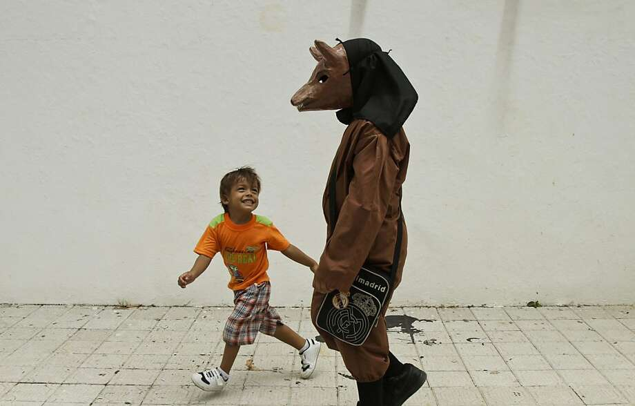 In Panama, devils look like kangaroos:A boy teases another boy wearing a traditional devil costume during Corpus Christi celebrations in the streets of La Villa, Panama. The custom of devils dancing in the street to pay penance and ask for relief from physical ailments dates back to the fifth century, when the Catholic Church used the dance to convert pagans to Christianity. Photo: Arnulfo Franco, Associated Press