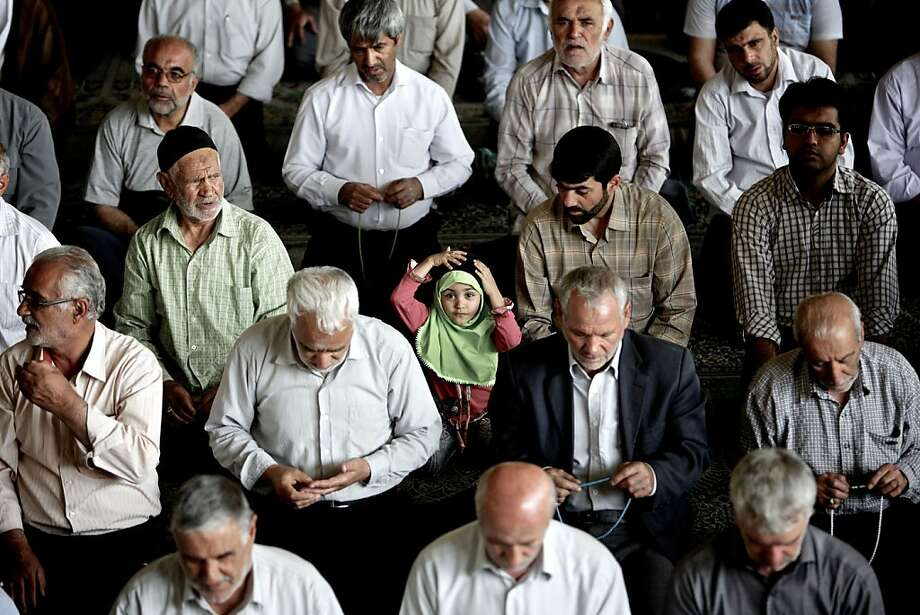 An Iranian girl adjusts her head-scarf as she sits amongst worshipers during the weekly Muslim Friday prayers at Tehran University in the Iranian capital on May 31, 2013. AFP PHOTO/BEHROUZ MEHRIBEHROUZ MEHRI/AFP/Getty Images Photo: Behrouz Mehri, AFP/Getty Images