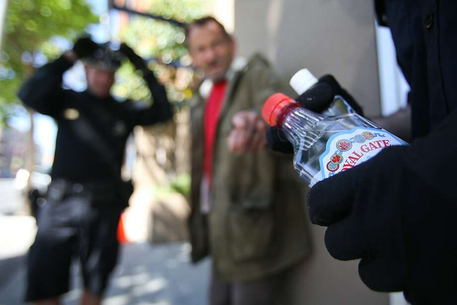 Officer Tim Faye displays vodka taken from a man sleeping it off on a sidewalk. The imbiber was taken to a sobering center and not cited. Photo: Mathew Sumner, Special To The Chronicle