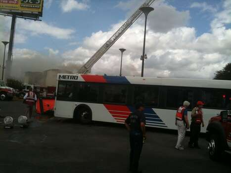 A Metro bus arrives on the scene of a fire on U.S. 59 Friday to act as a cooling station for firefighters. Photo: By Robert Stanton, Houston Chronicle