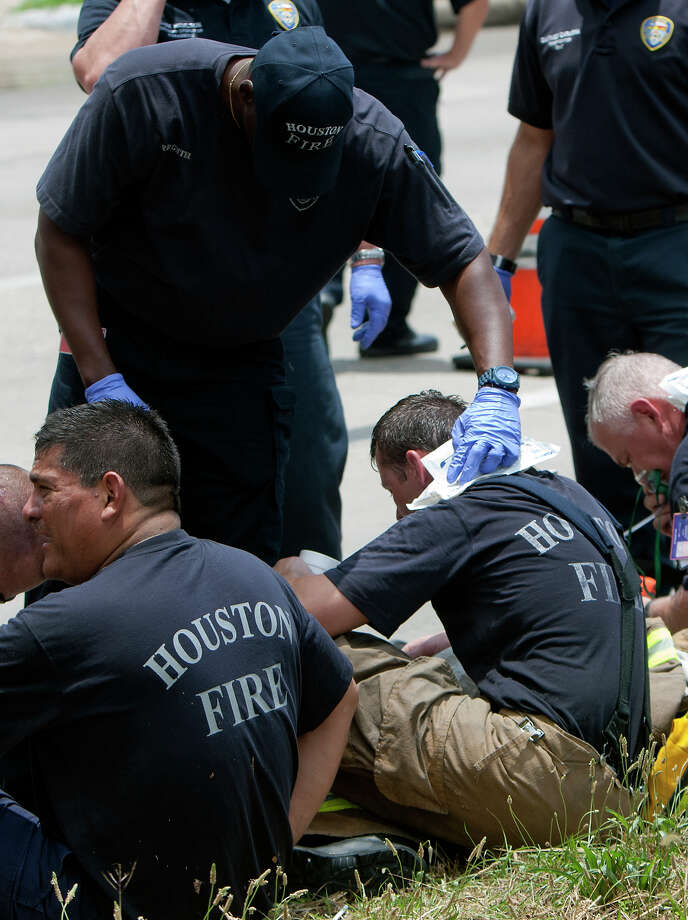 Firefighters rest during a 4-alarm blaze at the Southwest Inn on Hornwood drifts over motorists traveling the inbound lane of 59, Friday, May 31, 2013, in Houston. Four firefighters were transported in critical condition, and one was with a knee injury. Photo: Cody Duty, Houston Chronicle / © 2013 Houston Chronicle