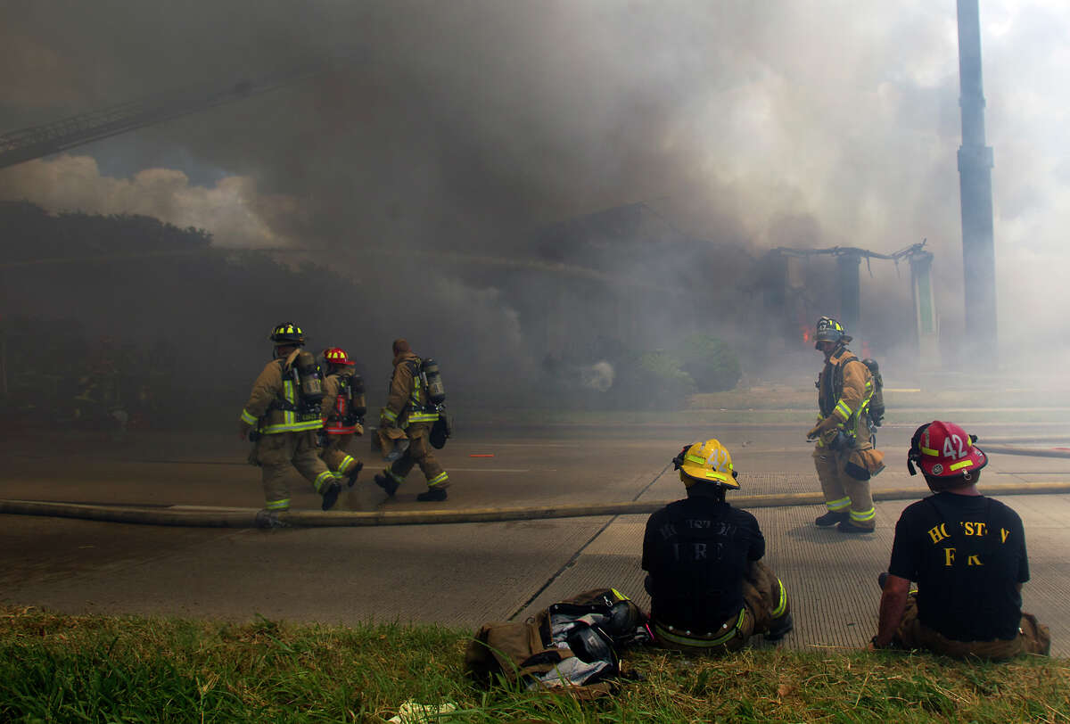 Smoke from a 4-alarm blaze at the Southwest Inn on Hornwood drifts over motorists traveling the inbound lane of 59, Friday, May 31, 2013, in Houston. Four firefighters were transported in critical condition, and one was with a knee injury.