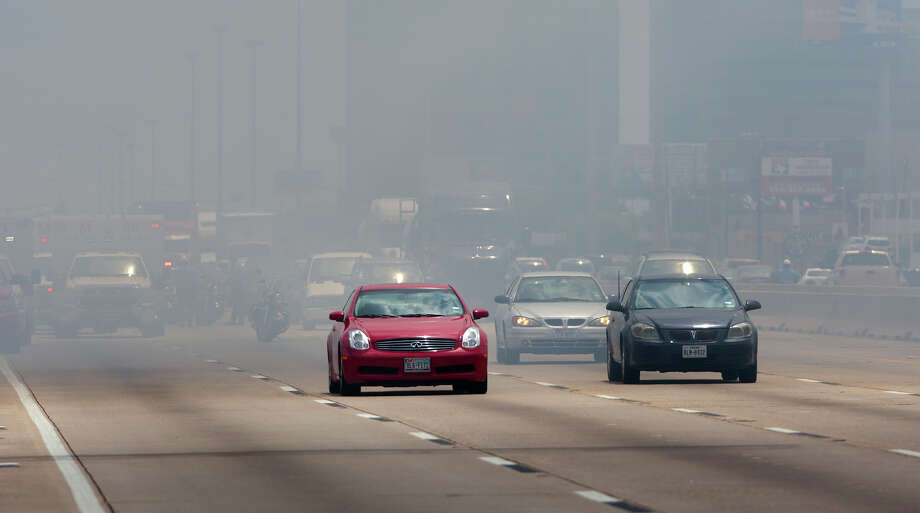 Smoke from a 4-alarm blaze at the Southwest Inn on Hornwood drifts over motorists traveling the inbound lane of 59, Friday, May 31, 2013, in Houston. Four firefighters were transported in critical condition, and one was with a knee injury. Photo: Cody Duty, Houston Chronicle / © 2013 Houston Chronicle