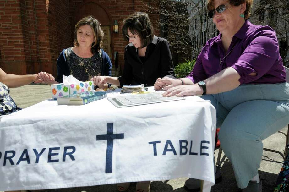 Deacon Susan Plaske, left, with All Saints Cathedral, and parishioners Beth Collum, center, and Jana Lingo, right, pray with a woman at the prayer table the women hold outside the church on Wednesday, May 1, 2013 in Albany, NY.   (Paul Buckowski / Times Union) Photo: Paul Buckowski