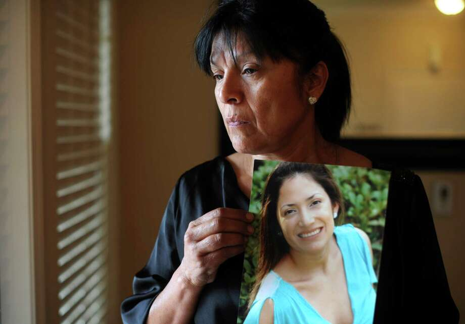 """Diana Segura displays a portrait of her daughter, Lisuli Jeanette """"LJ"""" Aguirre, who died after her car was swept away by flood waters on Rhapsody in San Antonio on Saturday, May 25. She had just finished working out with friends and was on her way to the Magnolia Pancake House. May 31, 2013. Photo: Billy Calzada, San Antonio Express-News / San Antonio Express-News"""