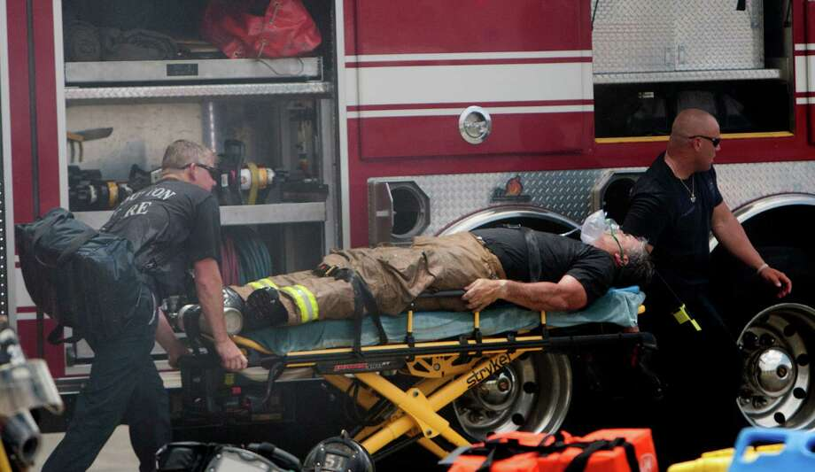 A firefighter is wheeled to an ambulance after fighting a 5-alarm blaze at the Southwest Inn on Hornwood, Friday, May 31, 2013, in Houston. Four firefighters were transported in critical condition, and one was with a knee injury. Photo: Cody Duty, Houston Chronicle / © 2013 Houston Chronicle