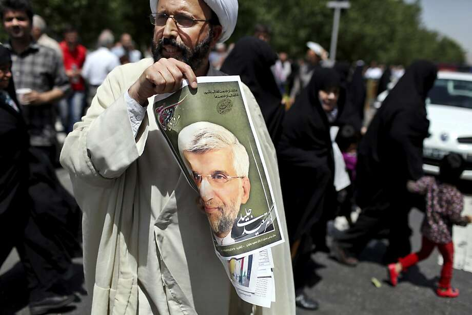 A cleric in Tehran holds up a poster of presidential candidate Saeed Jalili, Iran's top nuclear negotiator. Photo: Ebrahim Noroozi, Associated Press