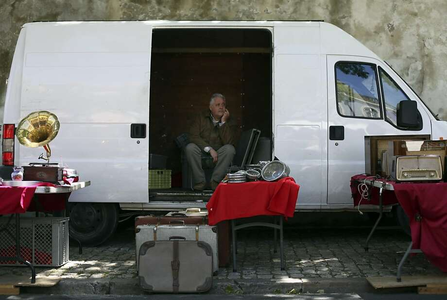 In this photo taken Saturday, April 27, 2013, Rafael Bernardino, 52, waits for customers at Lisbon's Ladra flea market. Bernardino, who uses his van as an office, has been selling second hand items for 13 years. Unemployment across the 17 European Union countries that use the euro hit another record high, the latest in a series of ignominious landmarks for the ailing single currency zone. Eurostat, the EU's statistics office, said Friday, May 31, 2013 that unemployment rose to 12.2 percent in April. After being stable at 17.5 percent in February and March, unemployment in Portugal rose to 17.8 percent in April. (AP Photo/Francisco Seco) Photo: Francisco Seco, Associated Press